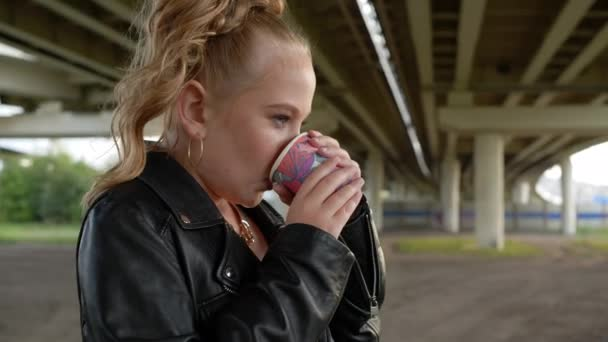 Rock girl drinking hot chocolate at cold day under car bridge. Young beautiful girl in black leather jacket trembling from cold. Model heating by hot tea at street.