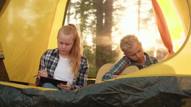 Teenager boy and girl in camping tent at summer hike. Girl painting in notebook. Boy playing music on guitar inside camping tent. Teenagers spending leisure on forest hike.