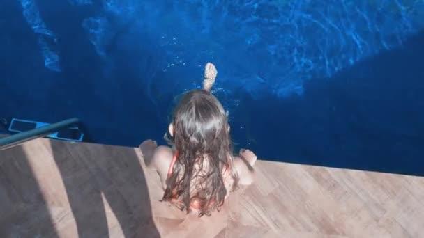 Dívka, která sedí na straně bazénu, se houpala v bazénu ve venkovním prostoru. Pohled shora dívka šplouchání nohama v modrém bazénu v letovisku Hotel.