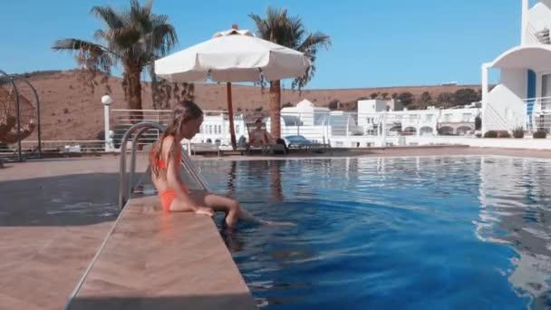 Egy fiatal lány, aki a medence szélén pihen a hotelben. Egy tinédzser lány lábat mártott az édesvízi medencébe. Turista lány élvezi a kék víz szabadtéri medence üdülőszálloda.
