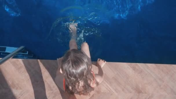 Top Down View of Girl Sitting near Swimming Pool