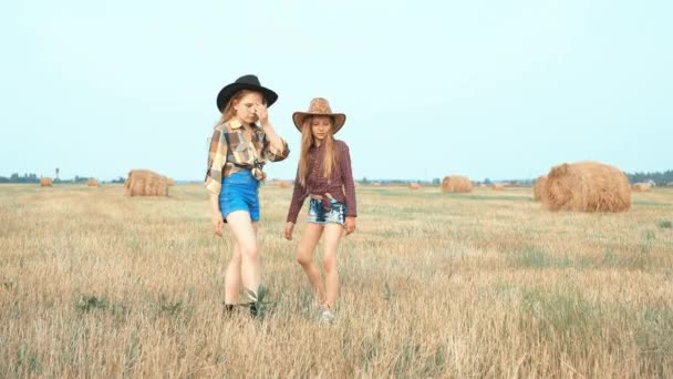 Cute girls in hats walking on field with haystacks