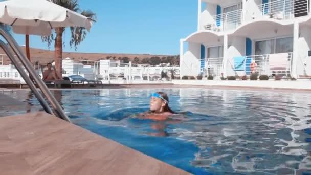 Tinédzser lány szemüvegben úszkál medencevízben nyári üdülőhelyen. Egy fiatal lány úszik az uszodában az üdülőhotelben. Turista lány pihentető trópusi szálloda.