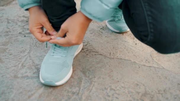 Nahaufnahme einer Person, die Schnürsenkel an blaue Turnschuhe bindet