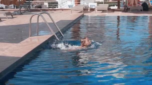 Adorable happy teenage girl swimming in outdoor pool
