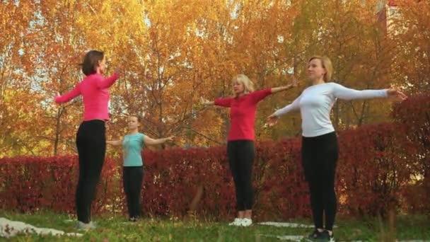 Női csoport jógázik az őszi parkban. Relaxáns nő edzés jóga ászana a szabadtéri edzés. Nők nyújtózkodnak jóga órán.
