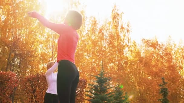 Yoga woman practising asana on outdoor workout. Fitness woman training yoga exercise in autumn park on sunshine background. Female group stretching on yoga class.