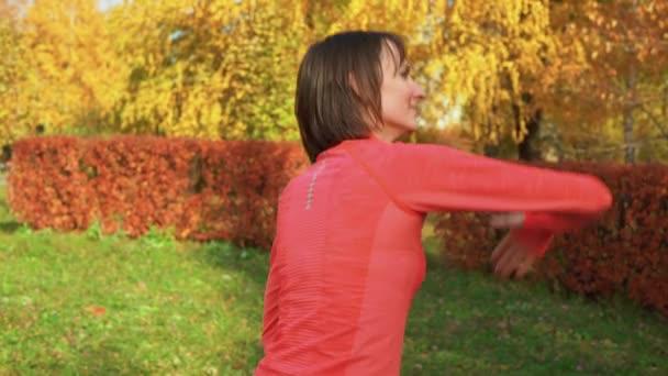 Sport nő táncol koreográfia órán az őszi parkban. Táncos nő edzés szabadtéri tánc lecke színes parkban ősszel.