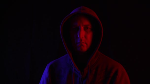 Man in dark hoodie looking up to camera on black background in blue and red lighting. Portrait mysterious man in hood in dark studio with red and blue backlight.