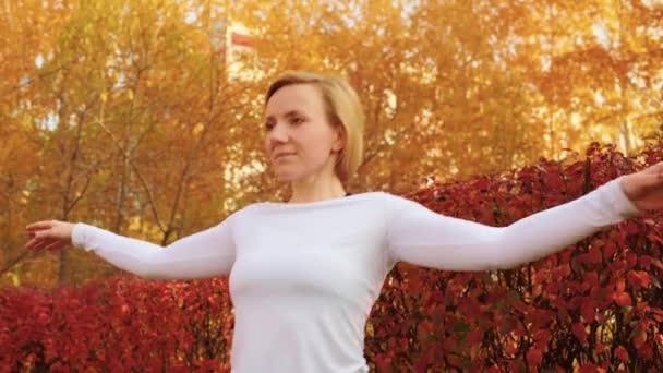 Gyönyörű mosolygós fiatal nő táncol és néz félre a parkban