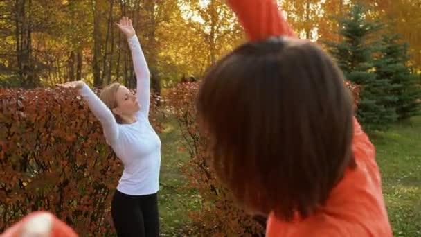 Fitness nő edzés jóga gyakorlat szabadtéri osztályban őszi parkban. Női csoport jóga-ászanát gyakorol a Városligetben. Sport nő edzés jóga edzés a parkban.
