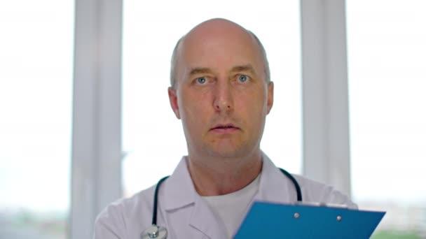 Porträt männlicher Arzt bittet Patient um das Ausfüllen medizinischer Formulare in der Klinik. Ärztin im Gespräch mit Patienten in Arztpraxis. Medizinischer Empfang im Krankenhaus.