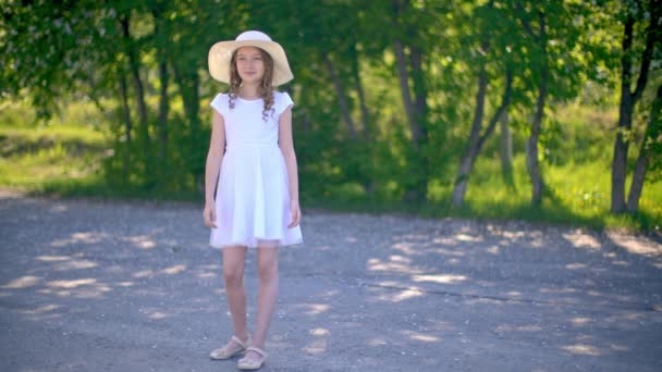 Young girl in white dress and hat standing on park alley on green trees background. Beautiful girl in summer park at sunny day. Romantic model in spring garden.