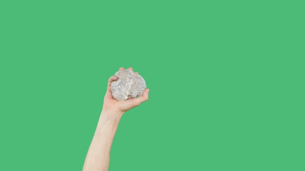 Human hand holding cobblestone on green chromakey background. Raised hand with stone on green screen background.