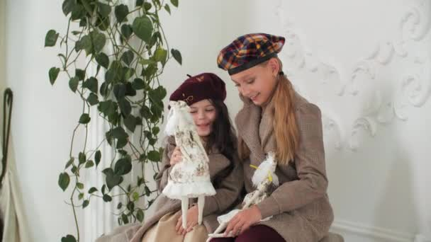 Adorable stylish girls in coats and berets posing with elegant vintage dolls