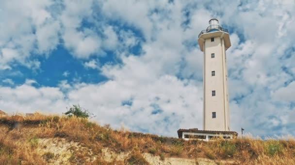 Leuchtturm auf Sanddüne gegen blauen Himmel mit weißen Wolken an Küste