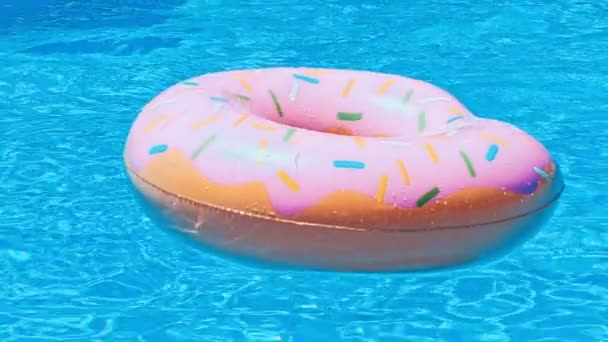 Ring floating in a refreshing blue swimming pool with waves reflecting in the summer sun. Active vacation background. Lifesaver for kid.