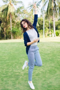 Young girl with short dark hair jumping in the park with palms. Girl wears blue trousers, grey shirt and blue jacket. She has black glasses on. Girl holds a smartphone and raises left hand in the air