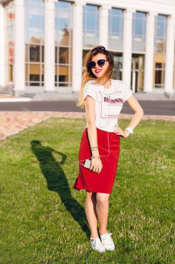 Full-height portrait of a standing smiling young girl holding a smartphone and listening to music on earphones. Girl wears a white t-shirt, red skirt and dark sunglasses. Girl is in the city center