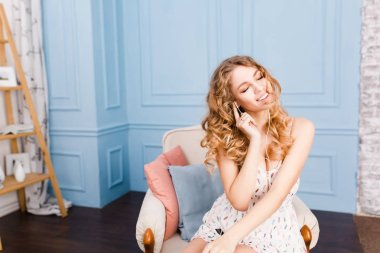 Cute girl with blond curly hair sits on armchair in studio with blue walls and brown furniture. She wears white dress. She listens to music on smartphone, smiles, holds her earphones with her hand