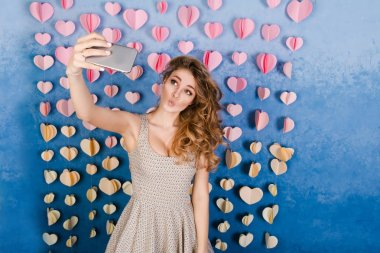 Cute sexy slim girl with blond curly hair standing in a studio with blue background and listening to music on earphones. She smiles, looks sexy and makes a selfie