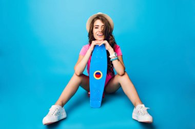 Pretty girl with long curly hair in hat posing on blue background in studio. She wears shorts, pink T-shirt. She seats on floor and holds skateboard between legs