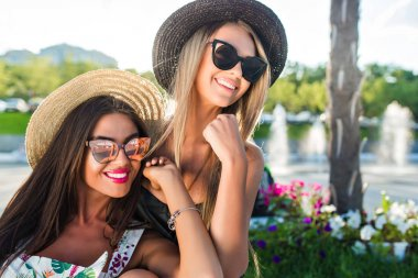 Close-up portrait of two attractive blond and brunette girls with long hair posing to the camera in park.  They wear summer clothes, hats and sunglasses. They are smiling to the side.