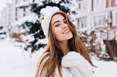 Stylish winter portrait of charming young woman with long brunette hair, in woolen white gloves and hat walking on street full with snow. Cheerful mood, smiling, waiting for christmas.