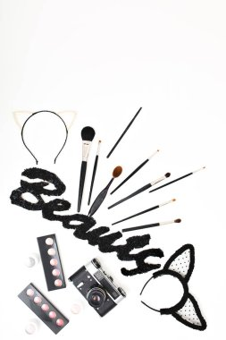Design set of stylish makeup stuff, woman accessories above on white background. Black inscription Beauty , shadows, retro camera, brushes, glamour set, cosmetic, stylist, hair hoop, carnival.