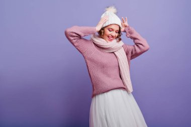 Wonderful girl in stylish white skirt posing with pleasure on purple background. Studio shot of cute short-haired young woman in hat and scarf smiling with eyes closed..