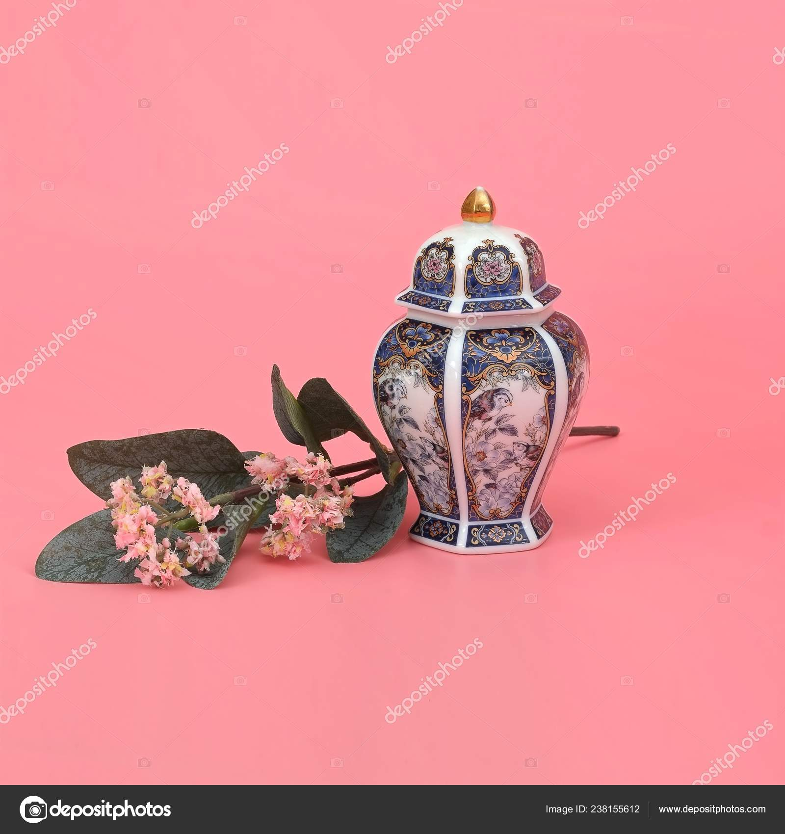 Classic oriental vase with jasmine branch isolated on pink (coral) background
