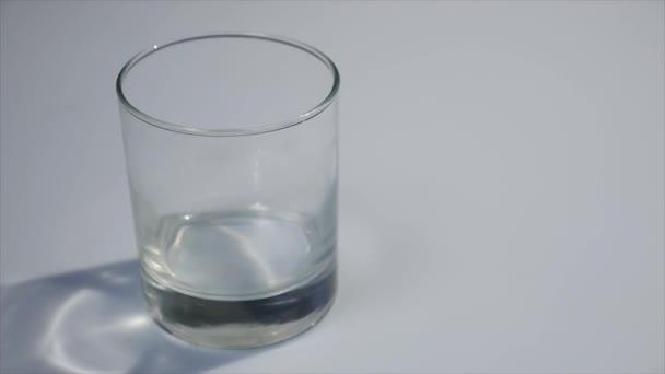 Nalévá mléko do skla. Bílé mléko zaplňují čiré sklo. Mléko proudí před bílým pozadím