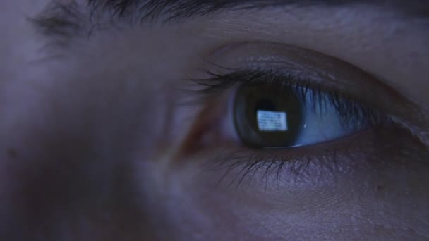 Detailní záběr z mans oči při pohledu na obrazovku pečlivě. Odraz obrazovky monitoru v žáků. Počítač a visí na internetu. Život v sociálních sítích
