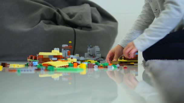 Malé děti si hrají se spoustou barevných plastových kostek