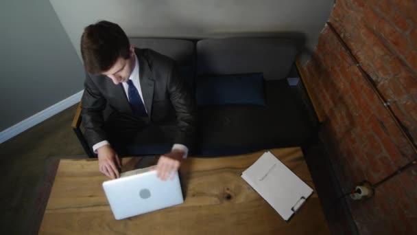 Podnikatel používá počítač v kavárně na dřevo stůl. pohled shora