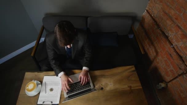 Üzletember használ laptop kávézóban a fa asztal. szemközti nézet