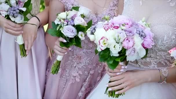 Nevěsta a družičky ve fialové šaty, drží jejich kytice