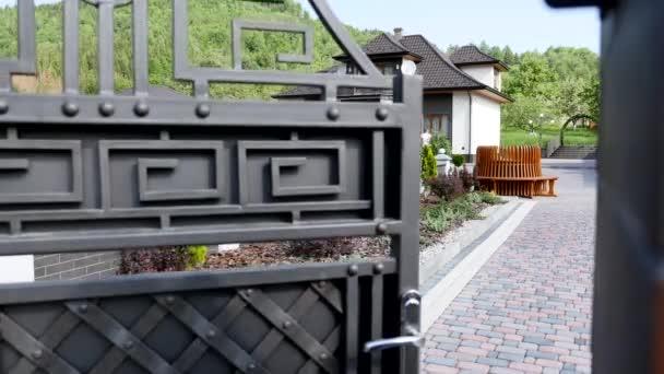 schöne Außenseite des neu erbauten Luxus-Eigenheims. Hof mit grünem Gras und Gehweg führen zu kunstvoll gestalteter überdachter Veranda und Haupteingang