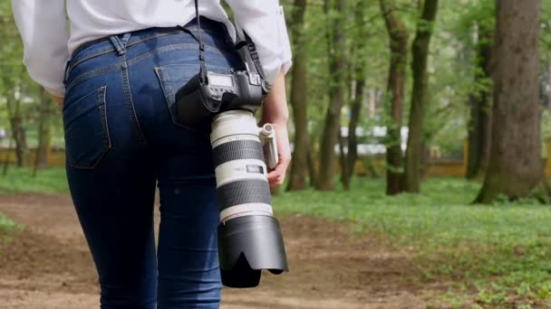 Young woman photographer working process shooting outdoors in park nature