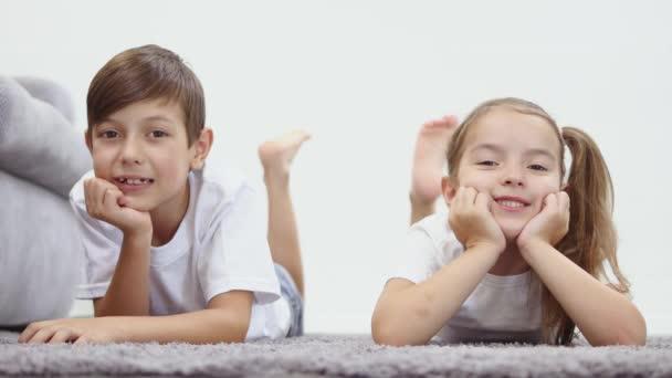 Niedliche lustige Kinder liegen zu Hause auf Teppich
