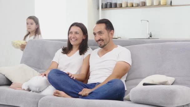 Mladý pár dívat se na televizi s popcorn v obývacím pokoji. děti přináší popcorn na gauči