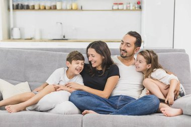 Family sitting on sofa smiling at camera on modern apartment background