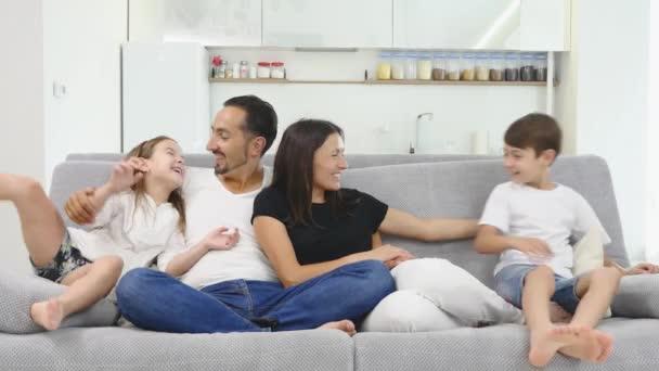 Mladá rodina sedí na gauči. Šťastná rodina tráví čas spolu doma. Matka, otec, syn, Dcera
