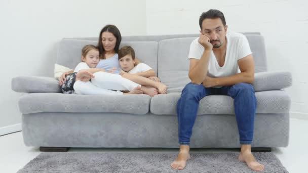 Hádáš v rodině. Smutný muž vpředu a jeho žena a dvě děti vzadu sedí na pohovce. Pohled zdola