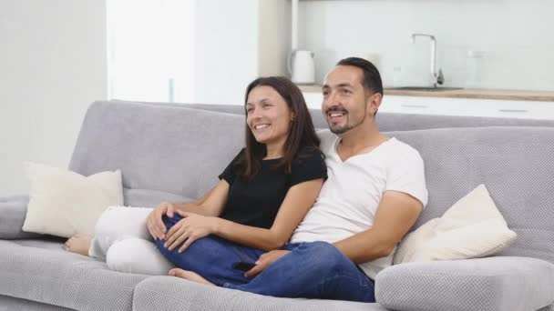 Giovane famiglia felice che si siede sul divano. Famiglia felice di trascorrere del tempo insieme a casa. Figlio che abbraccia e bacia la madre. Madre, padre, figlio, figlia