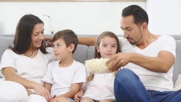 Šťastná rodina s dvěma dětmi doma, děti, bratr a sestra sledování filmu a s popcorn s rodiči