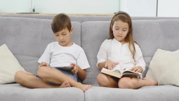 Happy siblings sitting on sofa at home. Boy play tablet and girl read book together