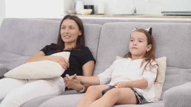 Mutter und Tochter haben viel Spaß und unterhalten sich beim Fernsehen im Wohnzimmer auf der Couch sitzend