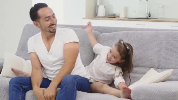 Dad with daughter playing and dancing on sofa at home