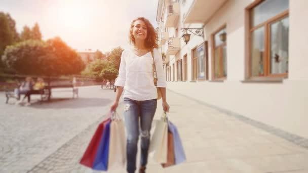 Šťastná žena s nákupníma taškama ve městě, zpomaleně. Sluníčko pozadí